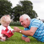 grandfather and grandaughter relax on grass
